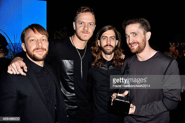 Recording artists Ben McKee Dan Reynolds Daniel Wayne Sermon and Daniel Platzman of Imagine Dragons pose backstage with their award for Favorite...