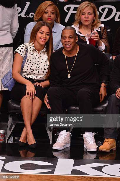 Recording artists Beyonce and JayZ react as they sit courtside at the Brooklyn Nets Vs Cleveland Cavaliers at Barclays Center on December 8 2014 in...