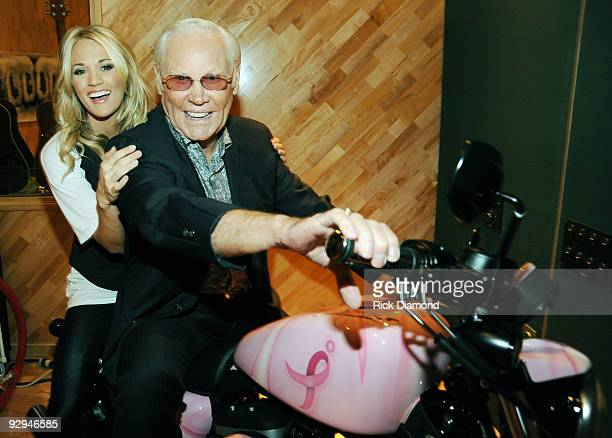 Recording Artists Carrie Underwood and George Jones pose on the Pink Harley XL883 Sportster being auctioned to help raise money for a breast cancer...