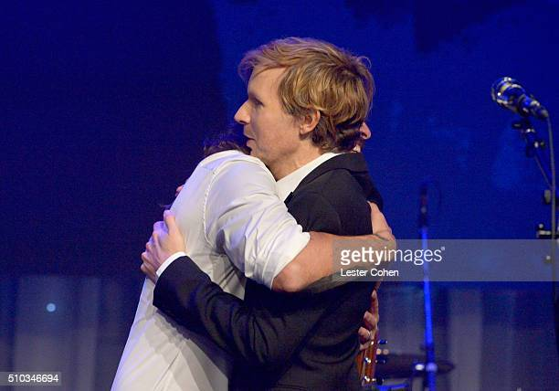 Recording artists Dave Grohl and Beck hug onstage after performing during the 2016 PreGRAMMY Gala and Salute to Industry Icons honoring Irving Azoff...