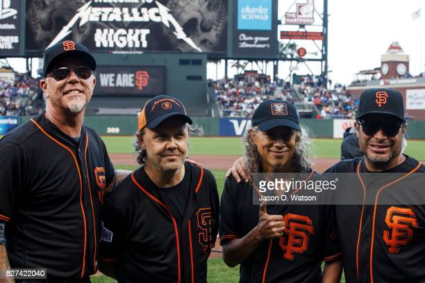 Recording artists James Hetfield Lars Ulrich Kirk Hammett and Robert Trujillo of the rock band Metallica stand on the field before the game between...
