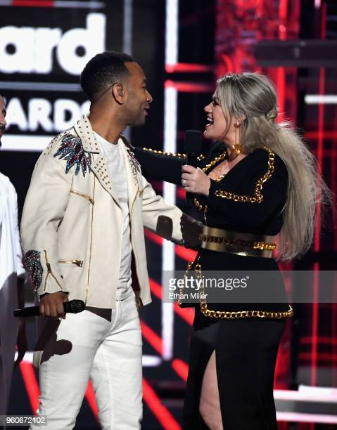Recording artists John Legend and Kelly Clarkson speak onstage during the 2018 Billboard Music Awards at MGM Grand Garden Arena on May 20 2018 in Las...
