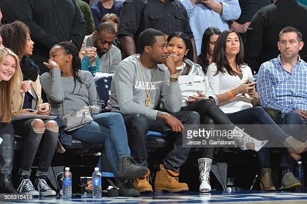 Recording Artists Meek Mill and Nicki Minaj look on during the Philadelphia 76ers against the Portland Trail Blazers at Wells Fargo Center on January...