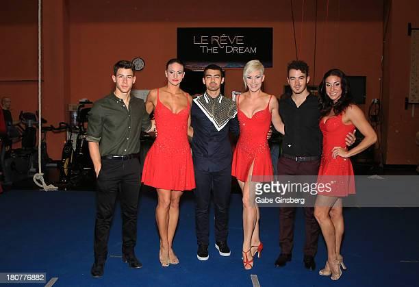 Recording artists Nick Jonas Joe Jonas and Kevin Jonas pose for photos with cast members of Le Reve at Wynn Las Vegas on September 14 2013 in Las...