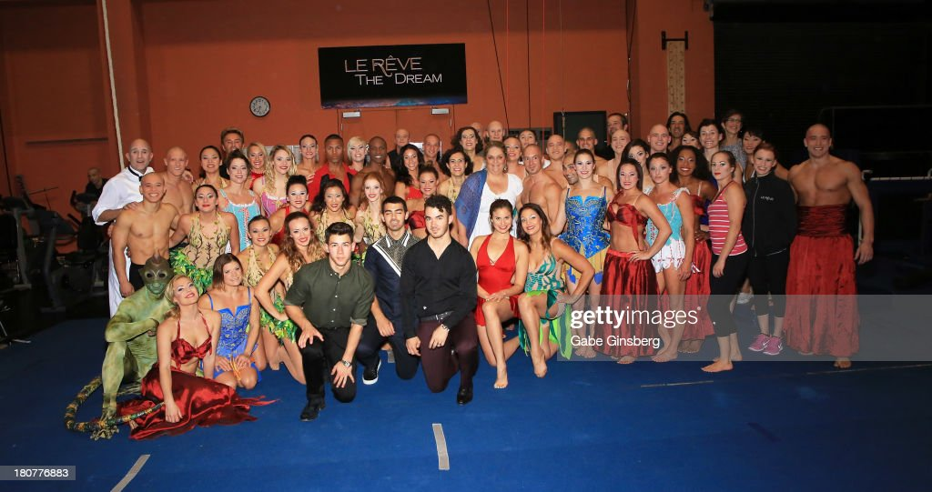 Recording artists Nick Jonas, Joe Jonas and Kevin Jonas pose for photos with cast members of Le Reve at Wynn Las Vegas on September 14, 2013 in Las Vegas, Nevada.