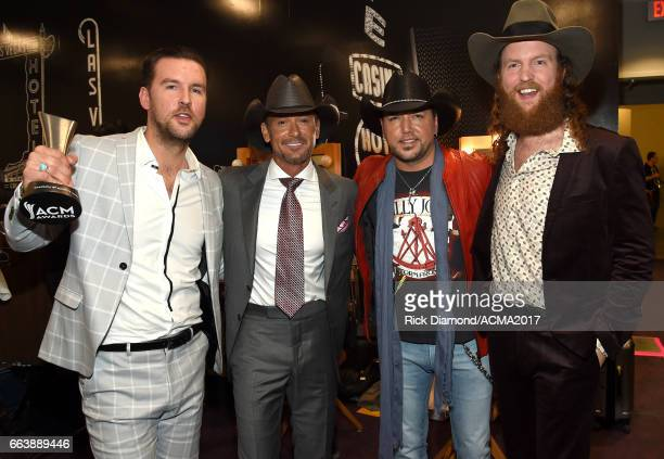 Recording artists TJ Osborne and John Osborne of music group Brothers Osborne pose with the award for 'New Vocal Duo or Group of the Year' with Tim...
