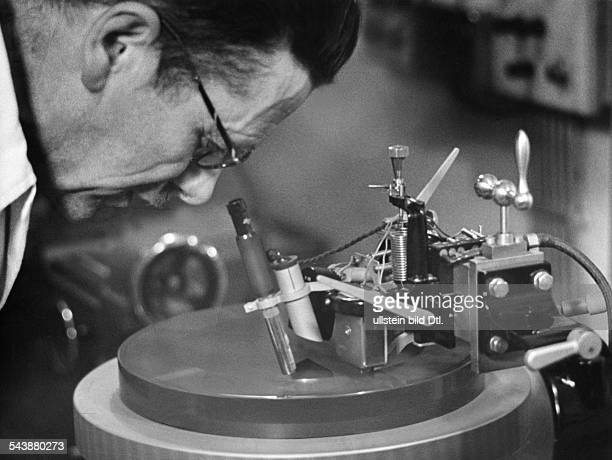 Recordmanufacturing Exposure technician is inspecting the cuts on the wax record Photographer Curt Ullmann Published by 'Hier Berlin' 21/1941Vintage...