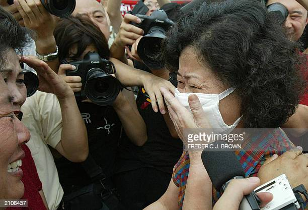 Recovered Severe Acute Respiratory Syndrome patient Hong Yu reacts upon seeing family members after being released from the Xiaotangshan SARS...