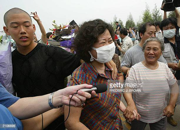 Recovered Severe Acute Respiratory Syndrome patient Hong Yu walks with family members after being released from the Xiaotangshan SARS Hospital on the...