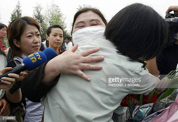 A recovered Severe Acute Respiratory Syndrome patient hugs a military medic upon release from the Xiaotangshan SARS Hospital on the rural outskirts...