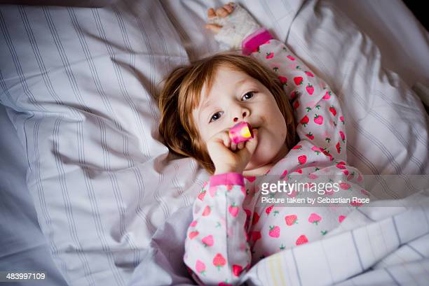 recovering at the hospital - girl in hospital bed sick stock photos and pictures