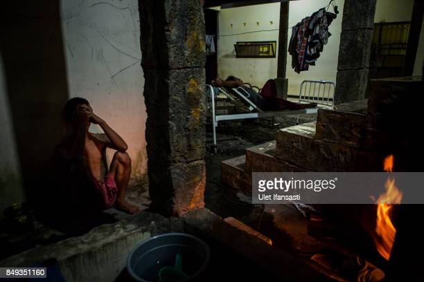 A recovering drug addict waits for his herbal hot water immersion treatment by the head of rehabilitation centre Ustad Ahmad Ischsan Maulana at the...