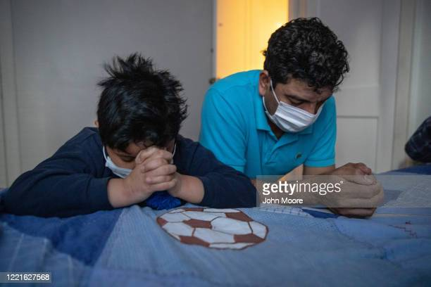 Recovering from COVID19 Guatemalan immigrants Junior and his father Marvin pray at home on April 24 2020 in Stamford Connecticut They have been sick...