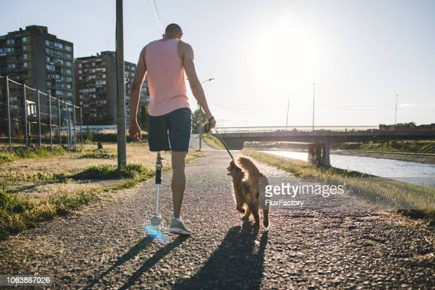 recovering man spending time with his dog by a river - amputee stock pictures, royalty-free photos & images