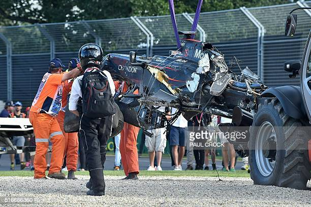 A recovery crew remove the car of McLaren Honda's Spanish driver Fernando Alonso after he was involved in a crash with Haas F1 Team's Brazilian...