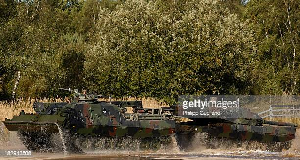 A recovery tank Bueffel tows a combat tank Leopard 2 A66 during the annual military exercises held for the media at the Bergen military training...