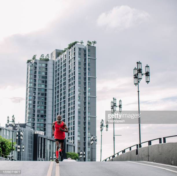 recreation for senior people: a mature african american man during his morning run - men wearing stockings stock pictures, royalty-free photos & images