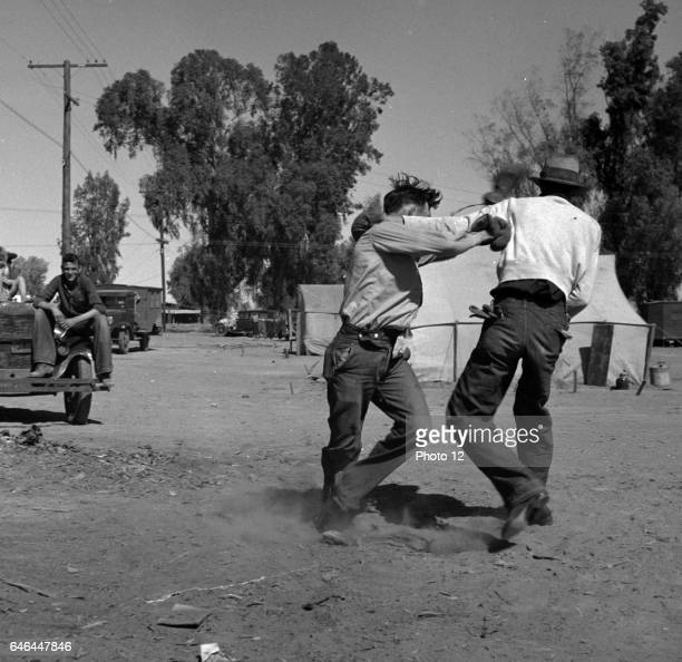 Recreation in a migratory agricultural workers' camp near Holtville, California by Dorothea Lange 1895-1965, dated 1939.
