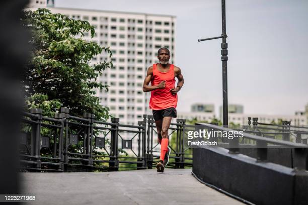 recreation in the 50s: senior man running in the city - center athlete stock pictures, royalty-free photos & images