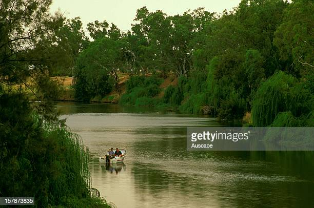 Recreational fishermen on the Macquarie River showing the riparian infestation with willow trees considered an environmental weed despite providing...