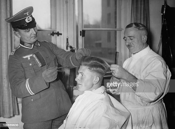 A recruit gets his hair cut under the survey of a Staff Seargant Germany Photograph November 4 1937