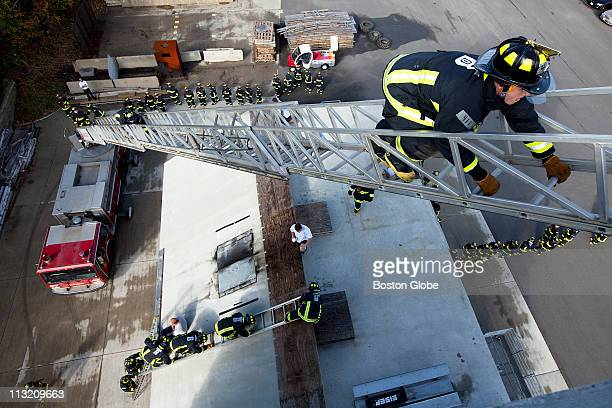 Recruits practice up and overs which consists of climbing up a ladder over its roof and down the other side of the building while another group of...