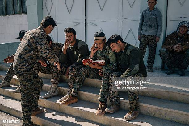 SDF recruits read a book written by Abdullah Ocalan outside the school where they attend classes on ideology before going through military training
