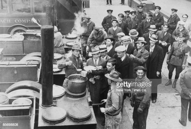 Recruits to a New Deal reforestation service receive a meal from a army soup kitchen at South Street New York City 4th August 1933