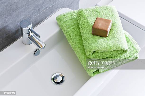 Rectangular bathroom sink with two green towels and soft soap