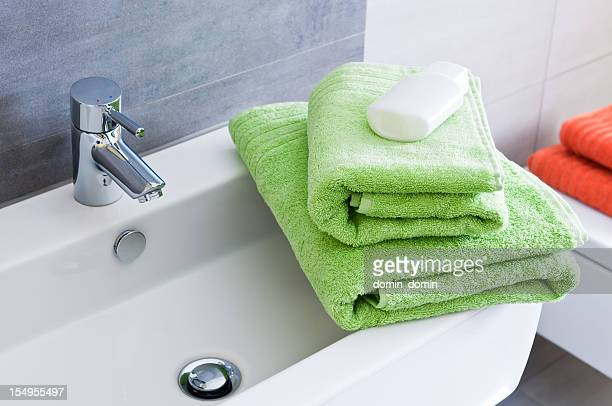 Rectangular bathroom sink with two green towels and white bottle