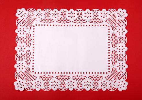 Rectangular doily on red cardboard 182459936