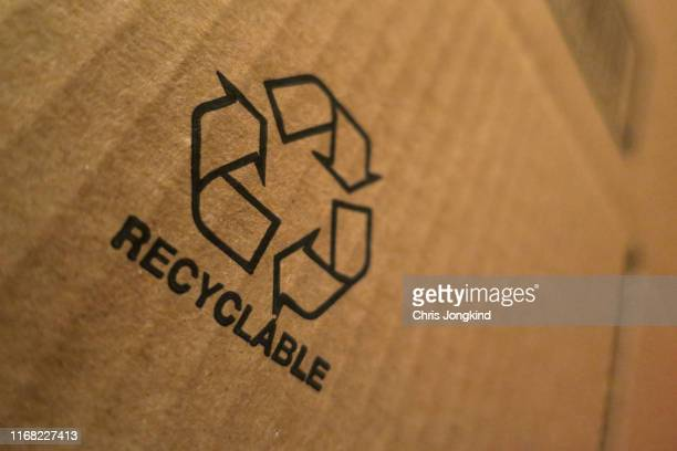 recyclable icon on cardboard box - recycling stock pictures, royalty-free photos & images
