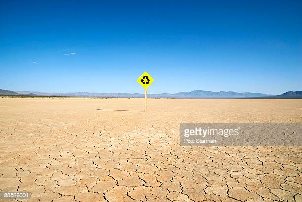 Recycle traffic sign on dry lake bed.