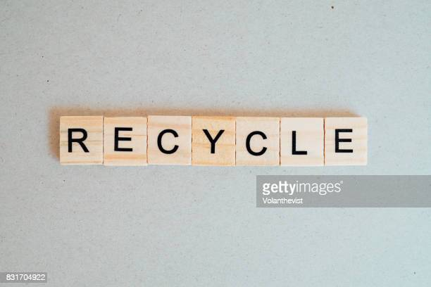 Recycle word in wooden letters on a recycled paper surface