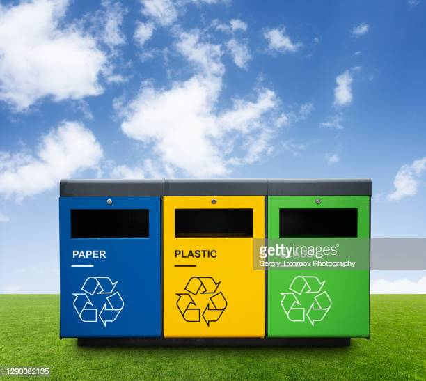 recycling bins on green grass with blue sky on background - rubbish bin stock pictures, royalty-free photos & images