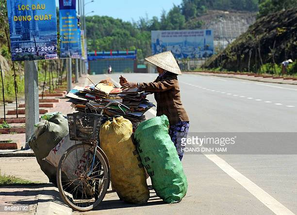 Recycling collector loads bags of what she has collected for sale along a road leading to Vietnam's first oil refinery at Dung Quat on February 22,...