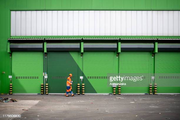 recycling facility workers walking outdoors in loading dock - loading dock stock pictures, royalty-free photos & images