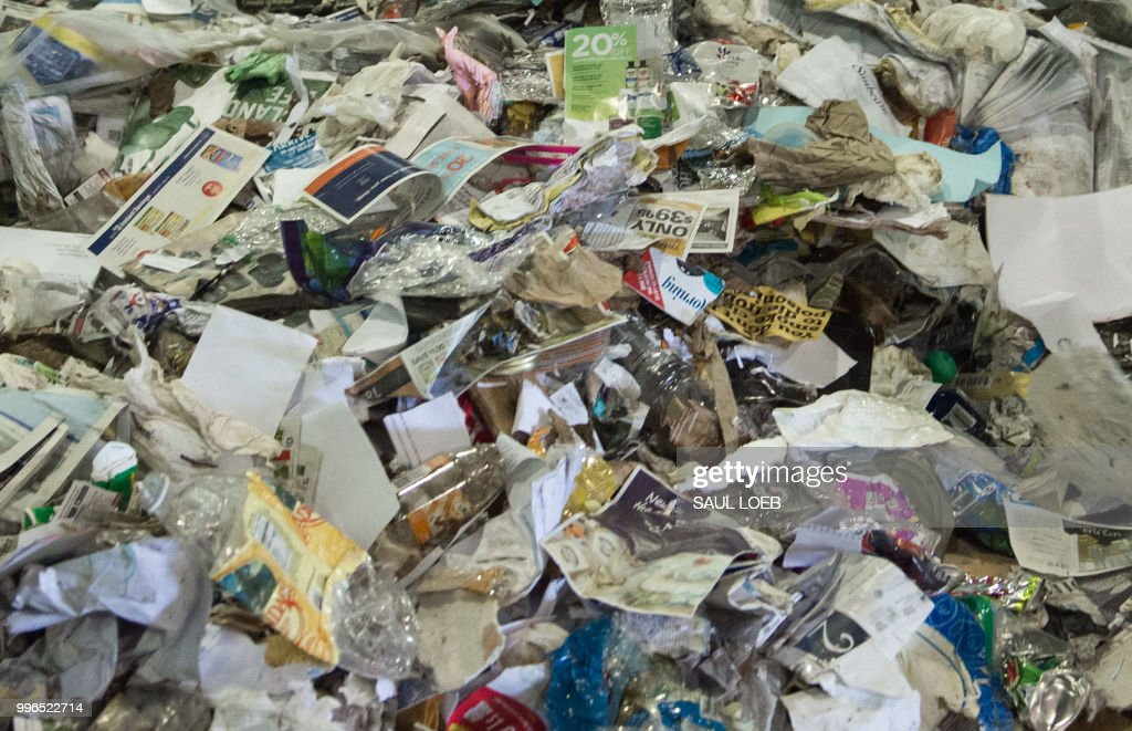 Recycling material moves along a conveyor belt to be sorted at the Waste Management Material Recovery Facility in Elkridge, Maryland, June 28, 2018. - Some 900 tons of trash are dumped at all hours of the day and night, five days a week, on the conveyor belts at the plant. For months, this major recycling facility for the greater Baltimore-Washington area has been facing a big problem: it has to pay to get rid of huge amounts of paper and plastic it would normally sell to China. But Beijing is no longer buying, claiming the recycled materials are 'contaminated.'