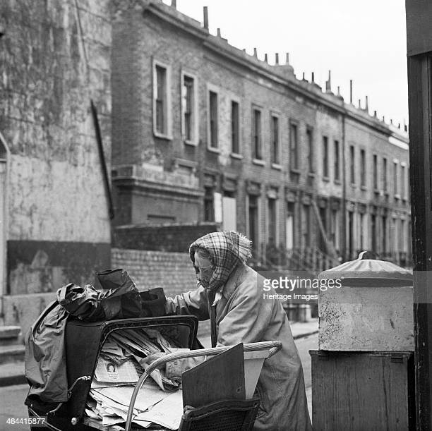 Recycling newspapers, Greater London, 1960-1965. A woman in raincoat and headscarf rearranging a pile of old newspapers in a pram. Behind her is a...