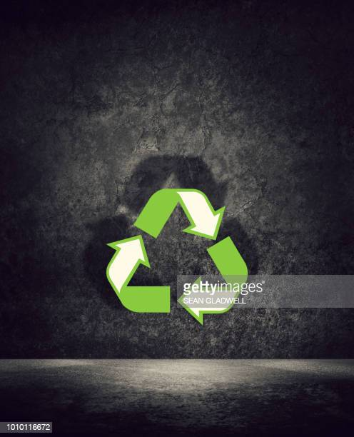 Recycling symbol in green in dark room