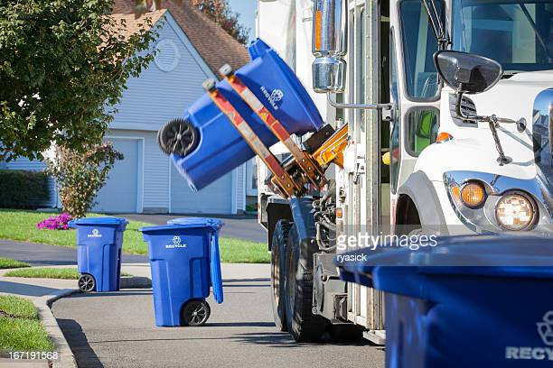 recycling truck lifting up container along neighborhood curb - curb stock pictures, royalty-free photos & images