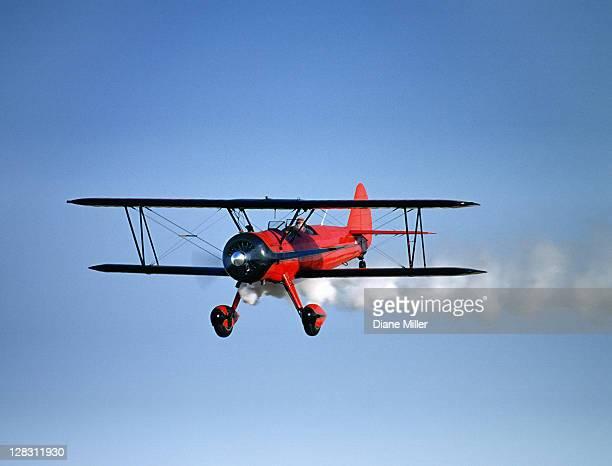 red 1943 stearman bi-plane in flight with tail smoke, st. francis, kansas, usa - doppeldecker flugzeug stock-fotos und bilder
