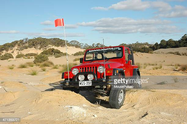 Red 1997 TJ Jeep Wrangler flexes on inland sand dunes