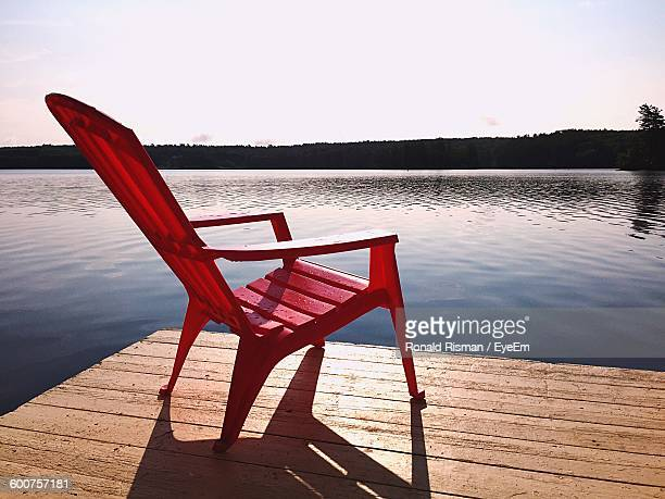 Red Adirondack Chair On Pier In Lake Against Sky