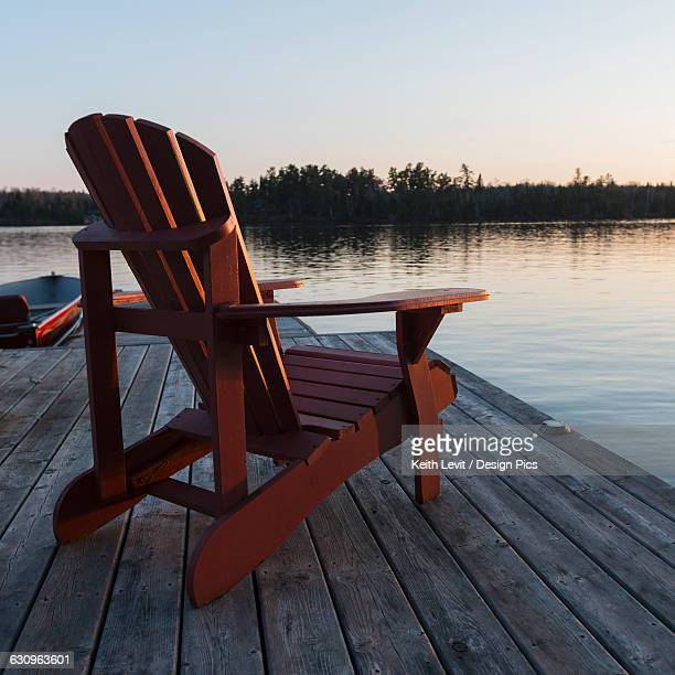 A red adirondack chair sitting on a wooden dock on a lake at sunset