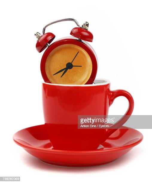 Red Alarm Clock In Coffee Cup Against White Background