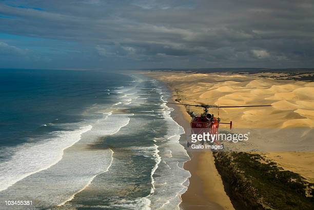 red alouette iii helicopter flying along coastline, algoa bay, eastern cape province, south africa - rescue worker stock pictures, royalty-free photos & images