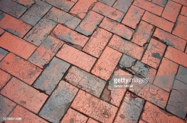 red and black brick paving in a herringbone pattern on an outdoor pedestrian walkway - herringbone floor stock photos and pictures