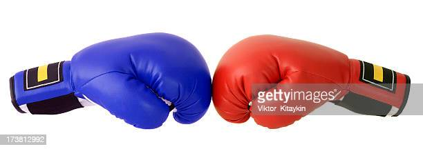 red and blue boxing gloves with a white backdrop - boxing gloves stock photos and pictures