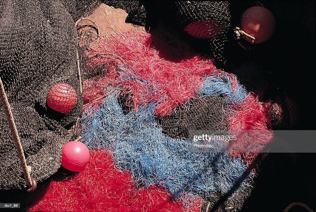 red and blue fishing nets sit tangled together with orange floats in the bottom of a boat : Foto de stock